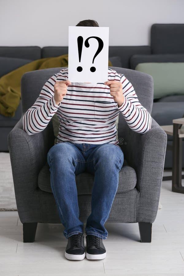 在纸片的年轻人掩藏的面孔与惊叫和询问符的后在家 免版税库存照片