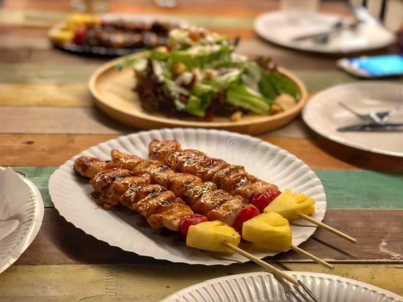 在纸白色盘的鸡烤肉在葡萄酒桌上 免版税库存图片