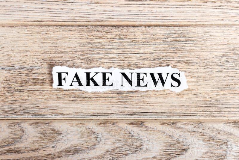 在纸的假新闻文本 在被撕毁的纸的词假新闻 com概念小雕象图象其它正确的常设文本 库存图片