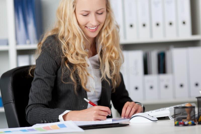 在纸的女实业家文字在书桌 免版税库存图片
