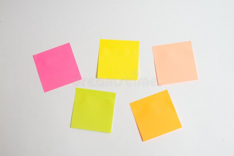 在纸的消息与事词互联网在笔记棍子的在与膝上型计算机和一杯咖啡的五颜六色的书在玻璃桌,顶面v上的 免版税库存图片