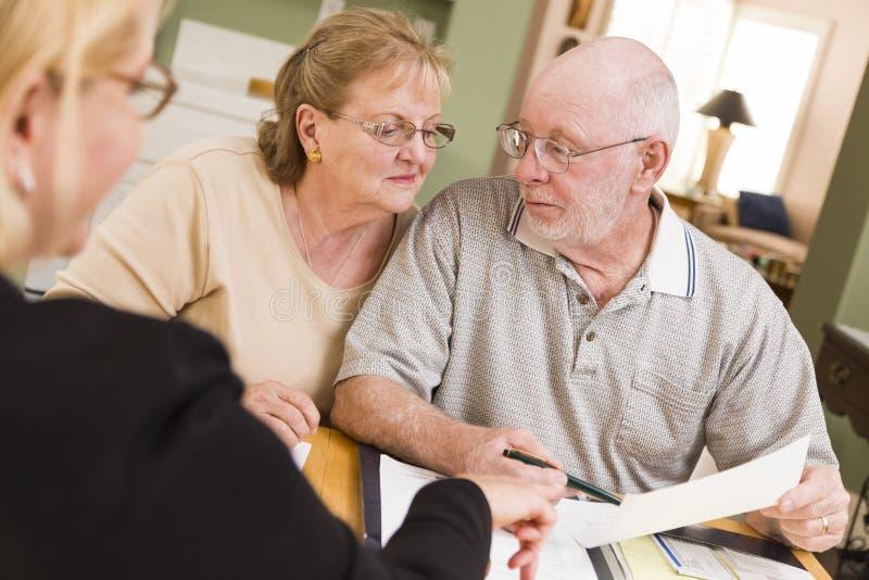 去在纸的资深成人夫妇在他们的有代理的家 免版税图库摄影