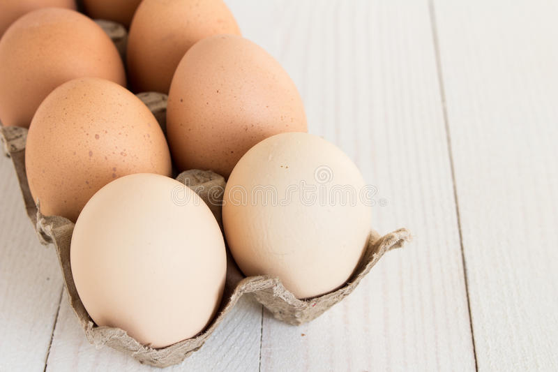 在纸盒包裹的新鲜的鸡蛋在白色木背景 库存图片