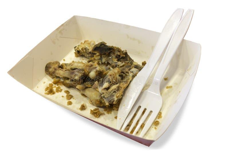 在纸碟的食品废弃部有塑料刀子和叉子孤立的 库存照片