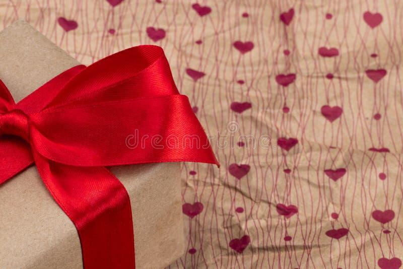 在纸纹理的礼物与心脏样式 华伦泰` s天backgr 免版税库存照片