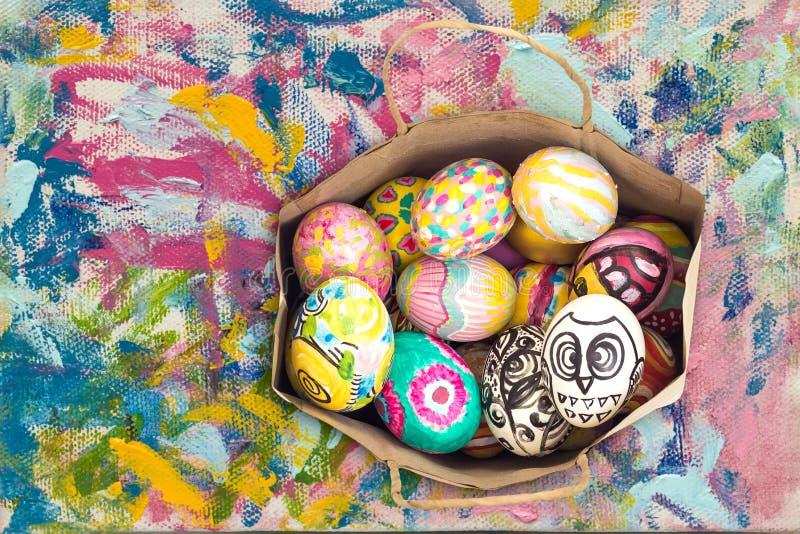 在纸袋的五颜六色的复活节彩蛋在五颜六色的绘画 库存照片