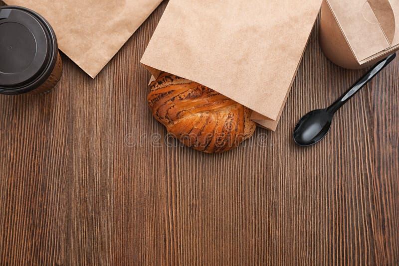 在纸袋的小圆面包和在木背景,顶视图的外卖食品 库存照片