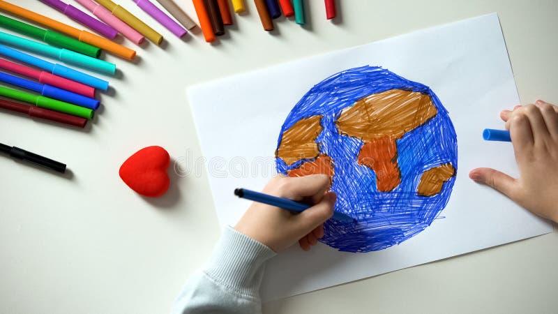 在纸,心脏的儿童绘的地球唱说谎在桌上,在世界的和平 图库摄影
