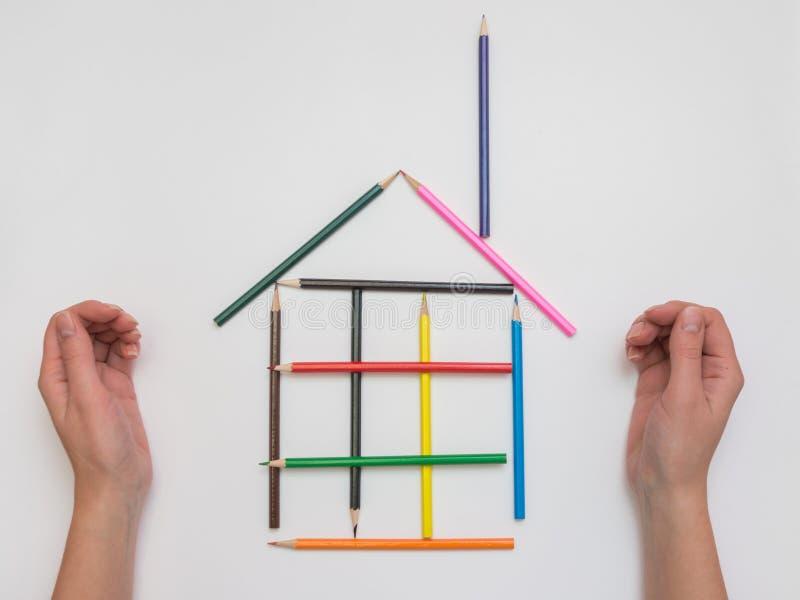 在纸滑稽的房子的女性手工制造铅笔 库存照片