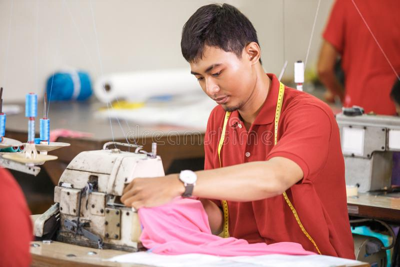 在纺织品工厂缝合使用工业缝合的m的亚裔工作者 库存图片