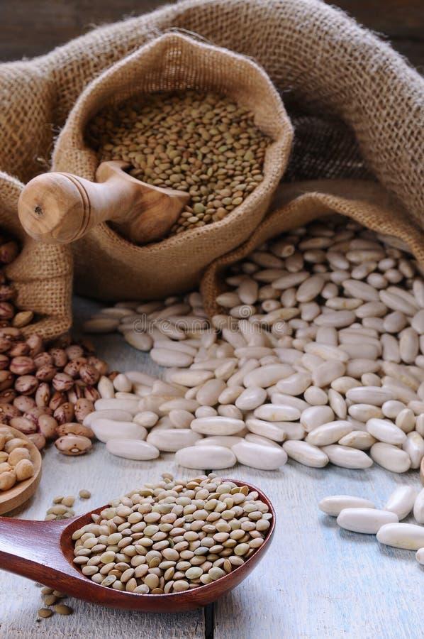 在纺织品袋子和匙子的各种各样的谷物 库存照片