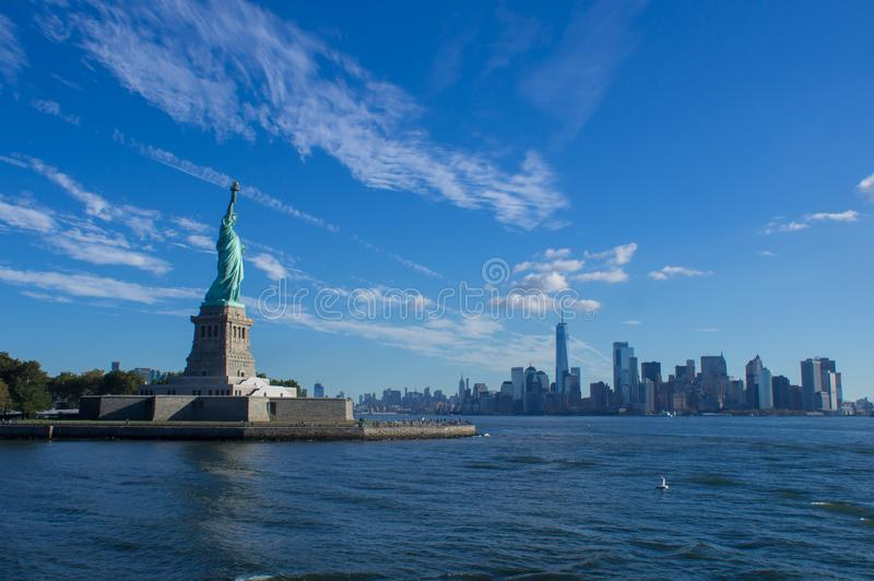 在纽约地平线前面的自由女神像 库存照片