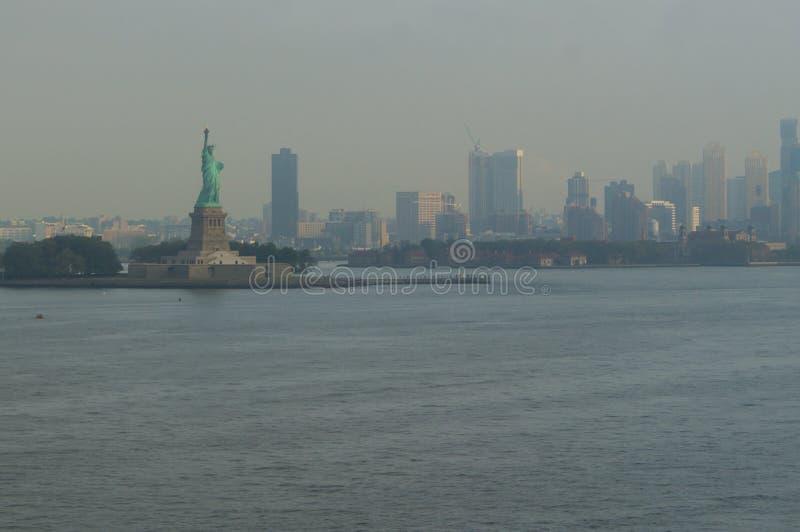 在纽约地平线前面的自由女神像 库存图片