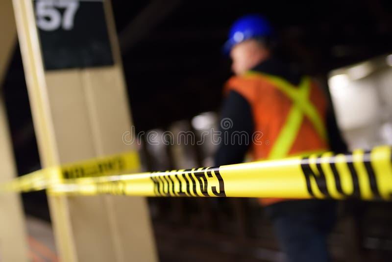 在纽约地铁的修理 NYC地铁的平台的MTA工作者在小心磁带后的 库存照片