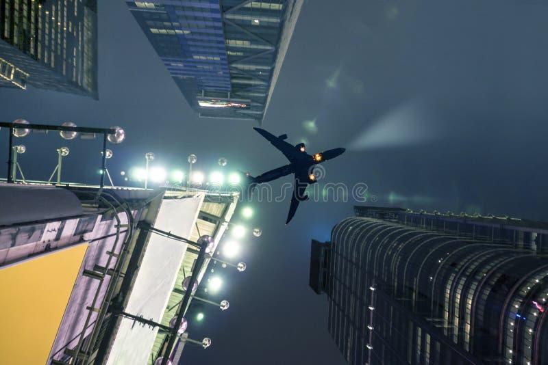 在纽约的平面飞行在与电天空上升大厦的晚上 免版税图库摄影