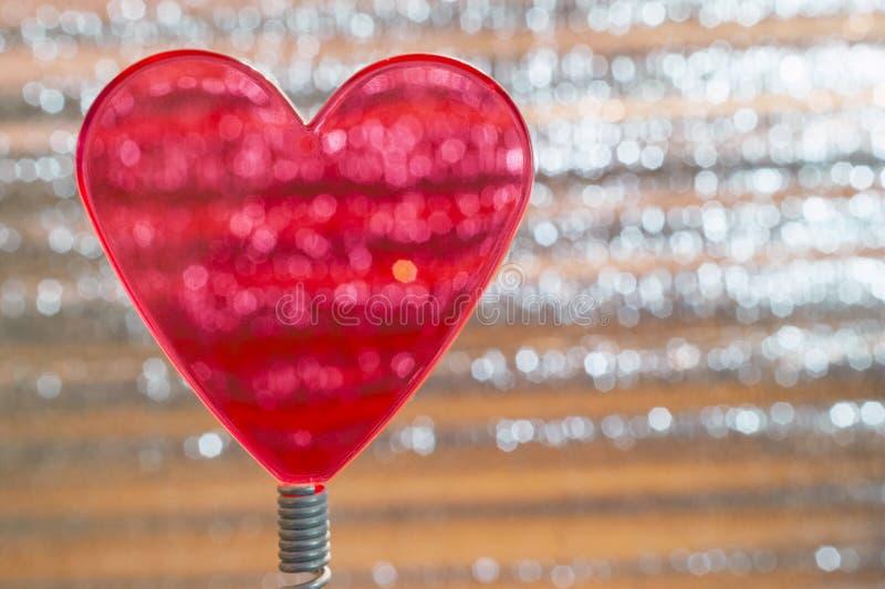 在线圈弹簧的清楚的红心 与有角度的银色发光的条纹的金属箔背景,橙色聚焦 情人节, 免版税库存图片