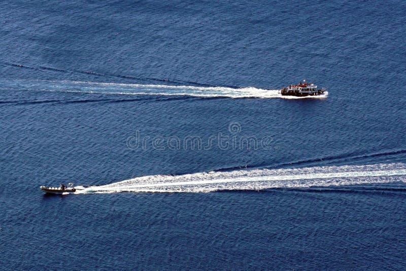 在组成一处Oia风景的破火山口的汽艇在圣托里尼 库存照片