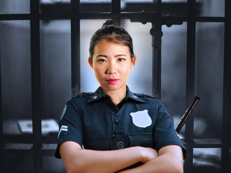 在细胞的年轻严肃和有吸引力的亚洲中国卫兵妇女身分在罪行的状态监狱佩带的警察制服 库存图片