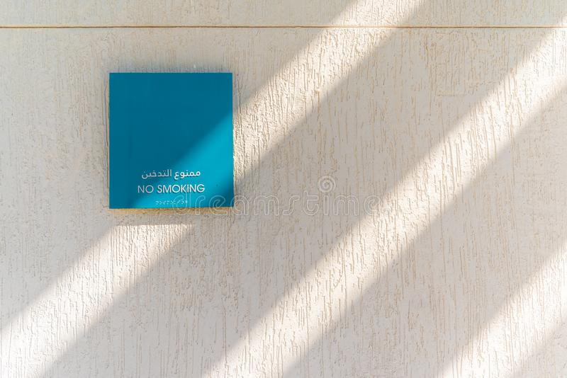 在织地不很细白色墙壁,阿布扎比上的禁烟标志 免版税库存图片