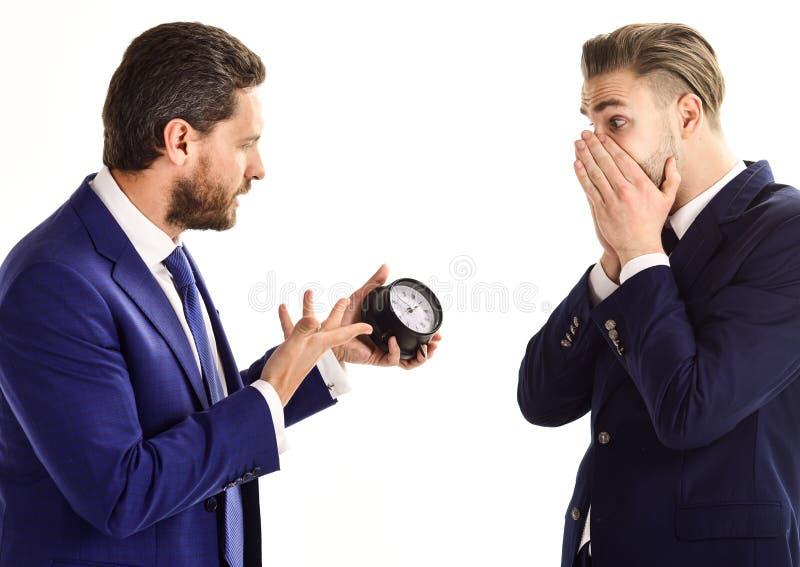 在经典衣服的商人拿着时钟手中 免版税图库摄影