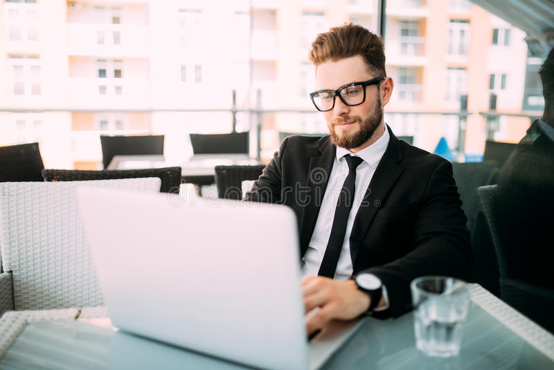 在经典衣服的英俊的有胡子的商人在城市时使用一台膝上型计算机并且采取笔记,当坐在咖啡馆 免版税库存图片