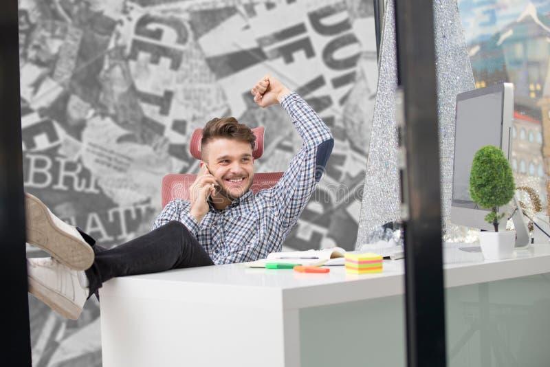 在经典衬衣的英俊的商人在办公室时使用一个智能手机并且微笑着,当与腿坐桌 库存照片