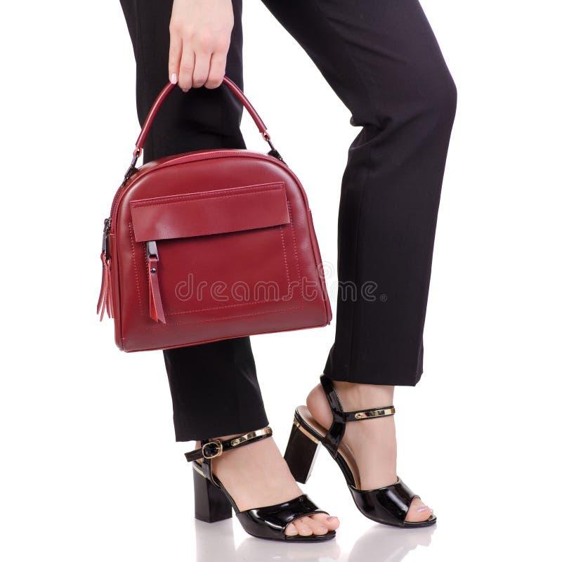 在经典黑色的女性腿在手中气喘有红色皮革提包的黑亮漆鞋子 免版税库存图片