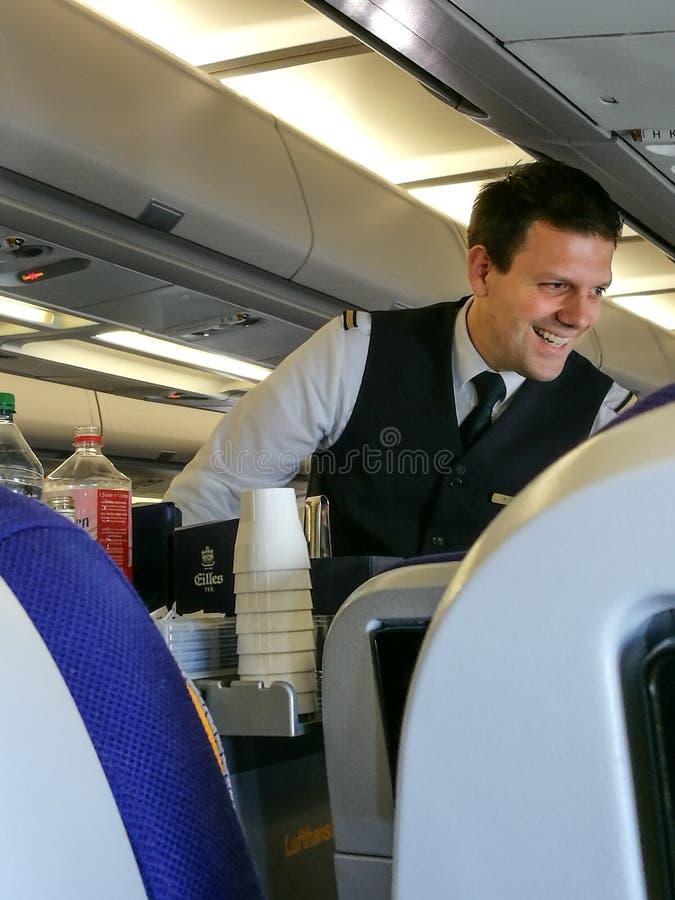 在经济舱的男性空服员服务 免版税库存照片
