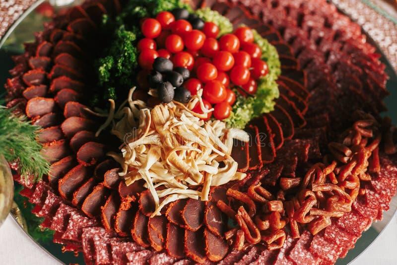 在结婚宴会的可口手指开胃菜桌 ?? 乳酪,肉,蕃茄,橄榄,绿叶,在桌上的沙拉顶视图 免版税库存照片