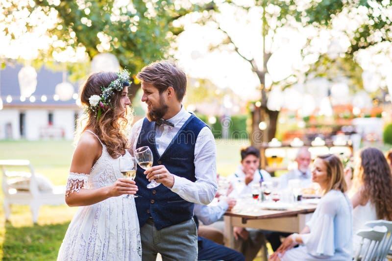 在结婚宴会的新娘和新郎使叮当响的玻璃外面在后院 库存图片