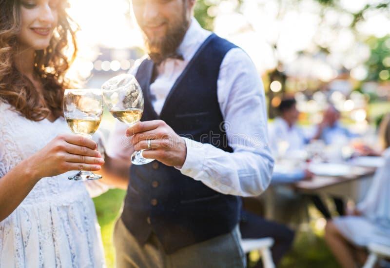 在结婚宴会的新娘和新郎使叮当响的玻璃外面在后院 免版税库存照片