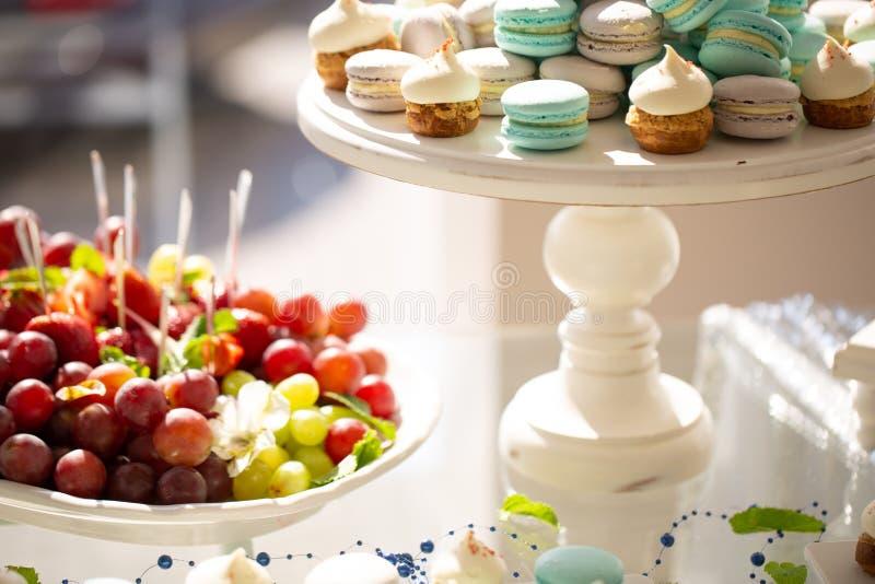 在结婚宴会蛋白杏仁饼干、杯形蛋糕和葡萄的可口和鲜美点心桌 免版税库存图片
