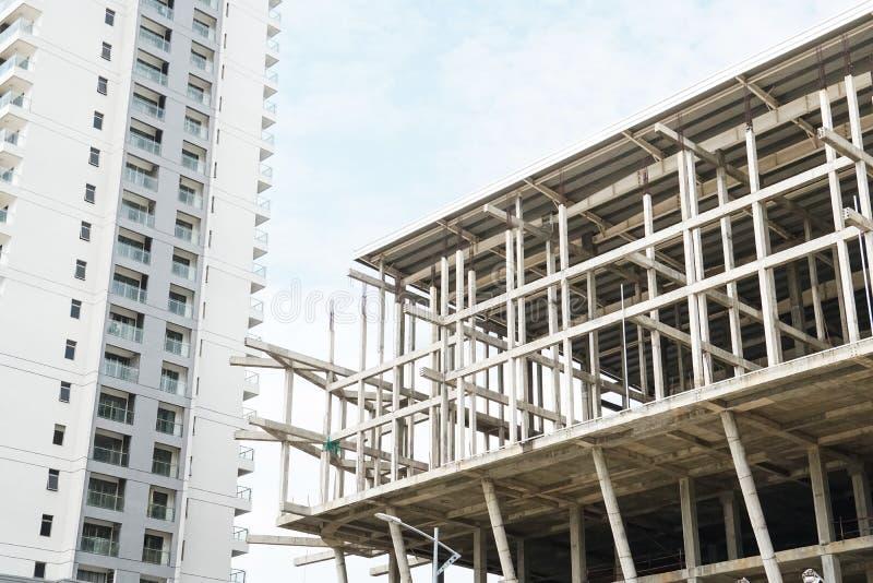 在结束完全公寓房公寓旁边的残缺不全的建造场所大厦建筑学结构 免版税库存照片