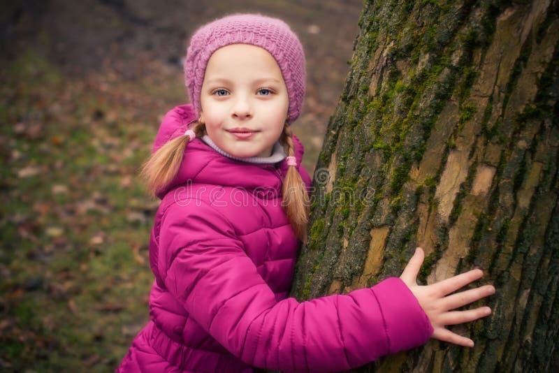 在结构树附近的小女孩在冬天公园。 免版税库存图片
