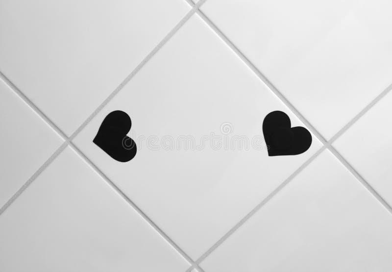 在给上釉的瓦片的两个小黑心形的贴纸 库存图片