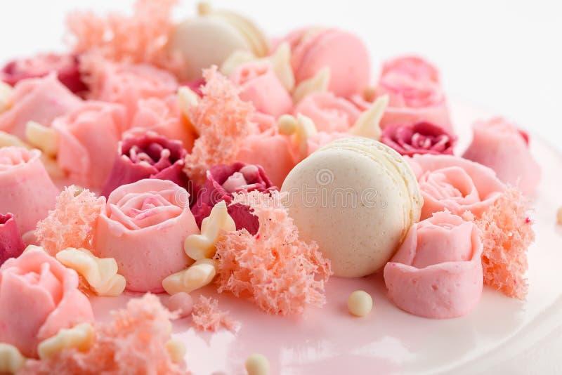 在给上釉的蛋糕的特写镜头桃红色奶油玫瑰色花装饰 免版税图库摄影