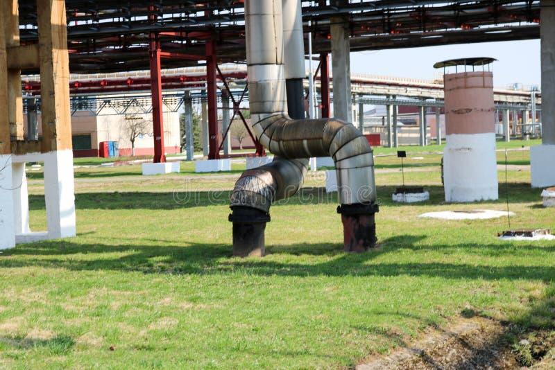 在绝缘材料的两个大管子由与红色ventil,电枢,阀门,在炼油厂的排水设备,石油化学制品,化学制品的锡制成 免版税库存照片