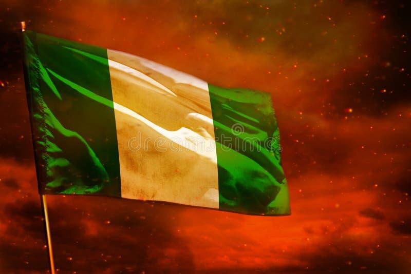 在绯红天空的振翼的尼日利亚旗子有烟柱子背景 麻烦概念 免版税库存照片