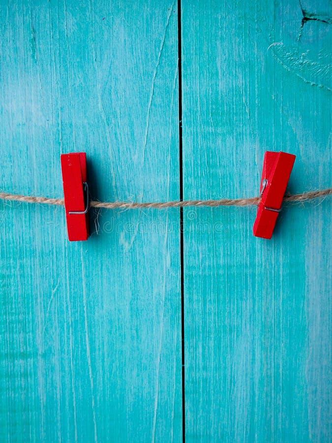 在绳索的两晒衣夹有木墙壁背景,葡萄酒夹子,红色晒衣夹 免版税图库摄影