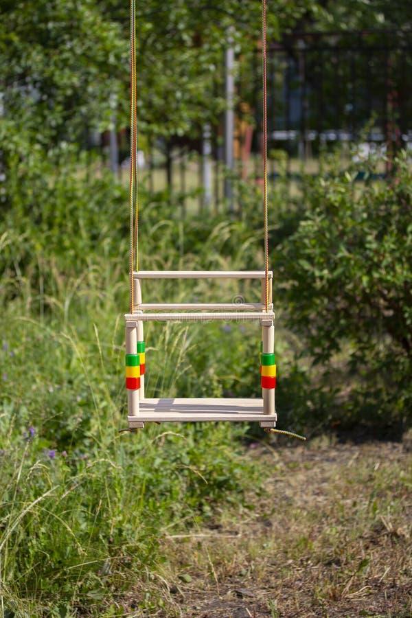 在绳索的儿童的木摇摆在公园绿叶背景垂悬  库存照片