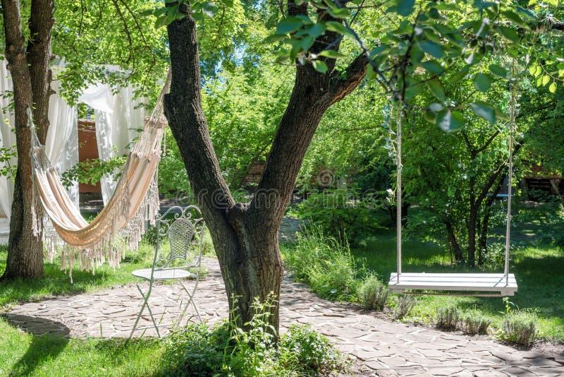 在绳索的木摇摆和吊床在大树下在庭院里 库存图片