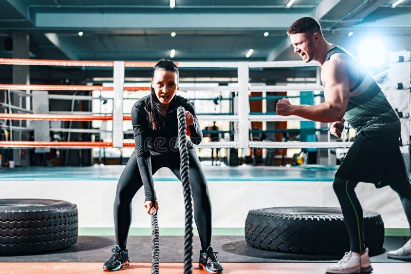 在绳索的运动妇女训练在健身房 男性教练员改变并且帮助达到成功 克服的概念 图库摄影