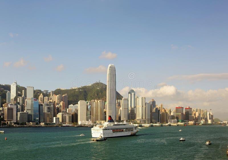在维多利亚港航行的船只和渡轮,在香港拥挤的摩天大厦中,标志性地标是显赫的 库存图片