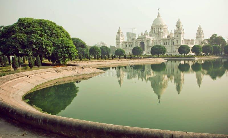 在维多利亚纪念堂附近的公园在加尔各答 在湖浇灌在纪念,历史宫殿附近在印度 免版税库存图片