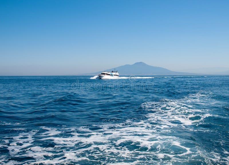 在维苏威火山前面的巡航小船在那不勒斯海湾索伦托度假胜地的 免版税库存照片