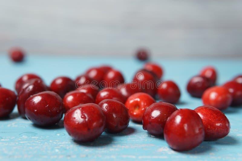 在绿松石木桌上驱散的红色甜樱桃 免版税库存照片