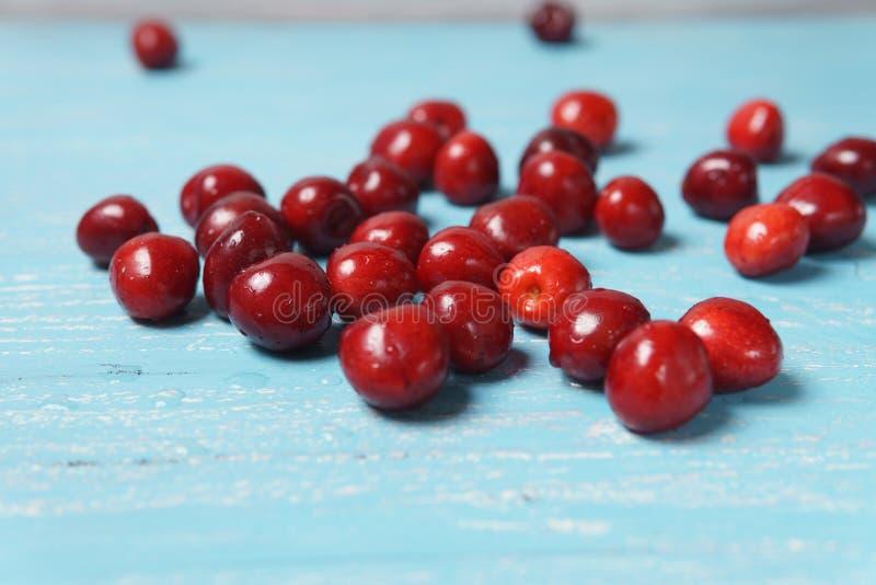 在绿松石木桌上驱散的红色甜樱桃 免版税图库摄影