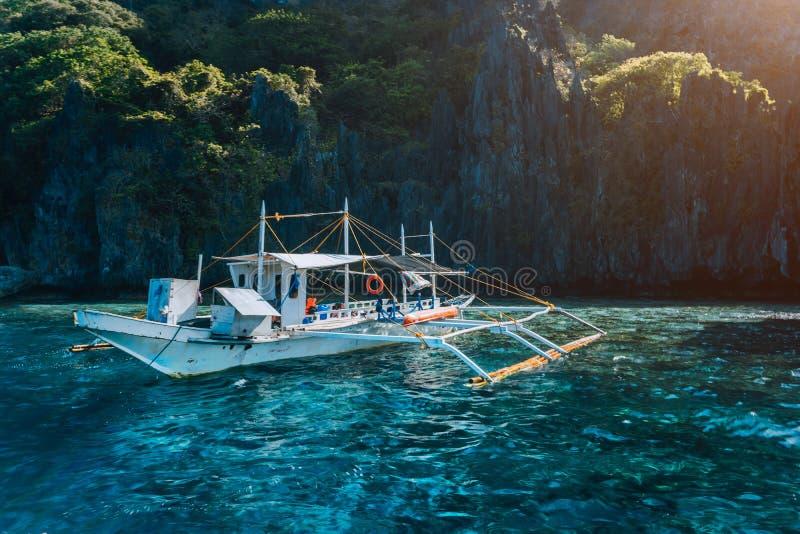 在绿松石水的邦卡地方小船反对巨大的石灰石峭壁 跳岛战术游览旅行 探索的菲律宾 库存图片