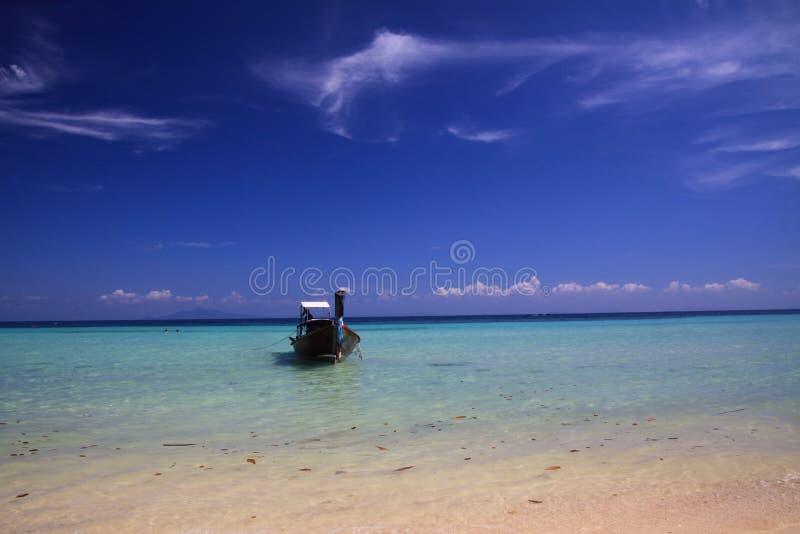 在绿松石浅水区的被隔绝的longtail小船弓在与少量卷云的天空蔚蓝下在热带海岛上 库存图片