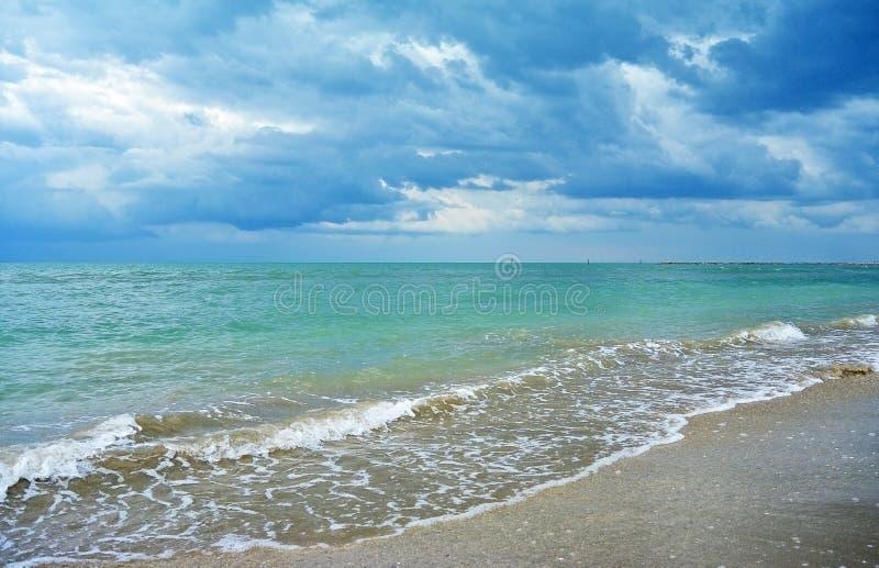 在绿松石海和沙子的黑暗的雨云靠岸 库存照片